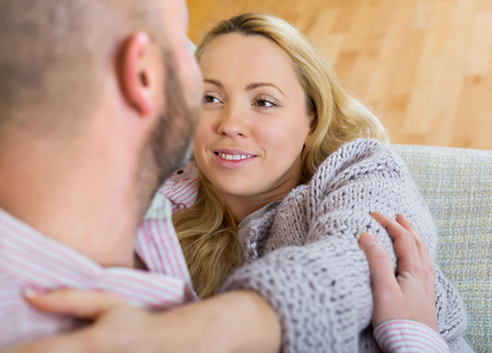 gladful: Smiling loving couple in living room at home Stock Photo