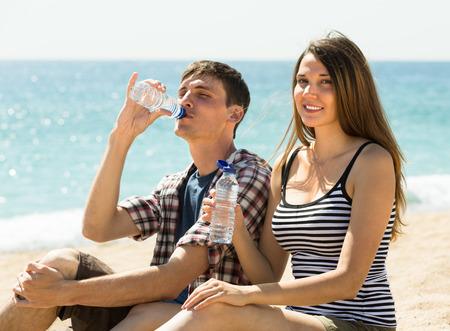 or thirsty: Pareja joven sedienta disfruta de una bebida refrescante de agua a la orilla del mar