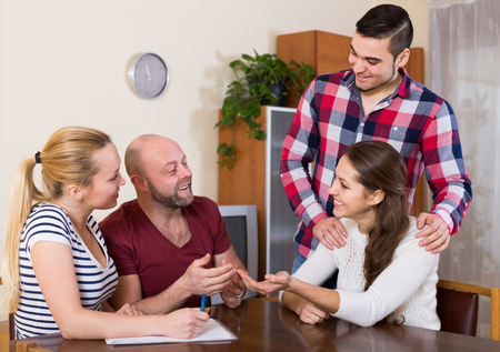 spouses: Young american spouses sitting with documents and asking friends for advice