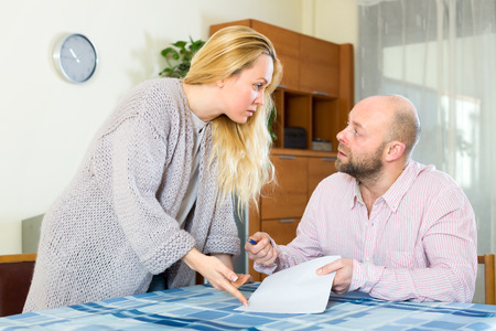 covetous: Married couple arguing on how to correctly fill in financial documents and forms