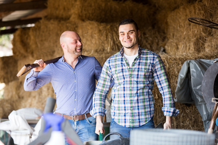 hayloft: Two smiling farm workers tedding the hay at hayloft. Focus on the right man