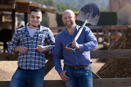 workmen: Two positive workmen posing with shovels near stables and smiling