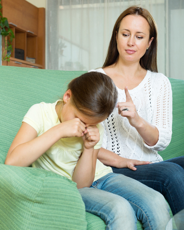 hysterics: Young woman scolding crying child at home interior