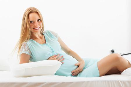 gravida: Happy pregnant woman awaking on white sheet   at home