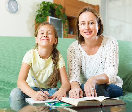 young schoolgirl: Mother with happy schoolgirl doing homework at home. Focus on girl