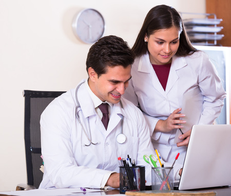 Intern asking advice from medical tutor at clinic reception Stock Photo