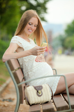 gravida: Pregnant woman sitting on a bench talking on the phone fun in the summer park Stock Photo