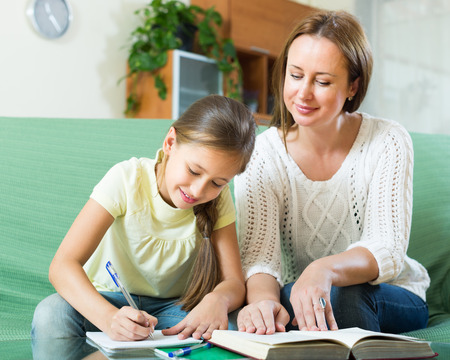 adult family: Mother with smiling schoolgirl doing homework at home. Focus on girl
