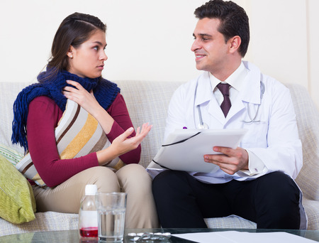 therapeutist: Young woman with cold and fever complaining to therapeutist