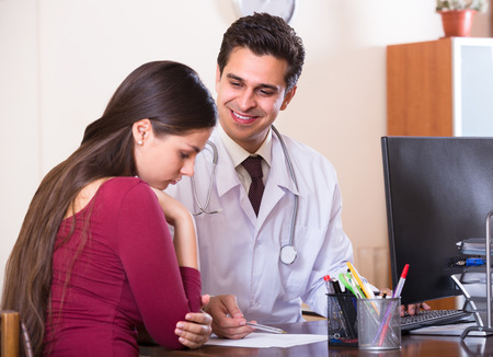 therapeutist: Portrait of young female patient and smiling therapeutist at desk in modern clinic Stock Photo