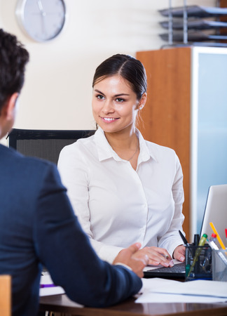 conduction: Banking positive russian agent listening to customer and smiling in agency