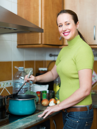 ordinary woman: Ordinary woman cooking soup with meat in kitchen at home and smiling Stock Photo