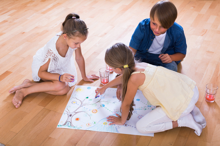 board game: Boy and two little girls playing at board game indoors