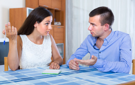 Sad young husband and wife discussing details of separation at home