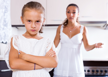 angry people: Portrait of quarrelling young woman and female child indoors