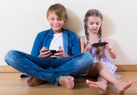 russian children looking at screen of modern smartphones indoors
