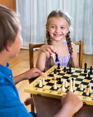 smart girl: Happy boy and little girl playing chess at home Stock Photo