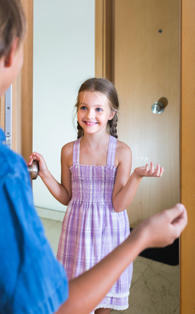 expected: Hospitable american child receiving expected friend at home interior. focus on girl Stock Photo