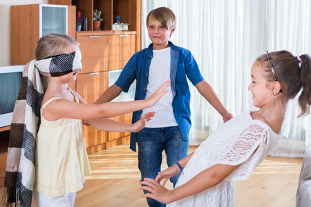 blind man: smiling children playing at Blind man bluff indoors Stock Photo