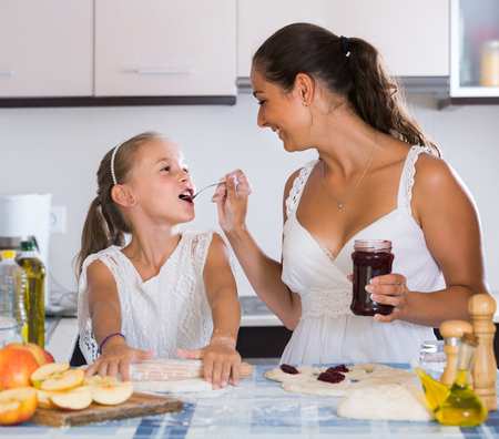 mum and child: Portrait of happy american woman and child cooking sweet pies Stock Photo