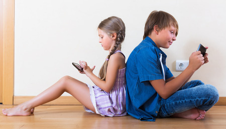 smiling teenagers: Happy little girl and teenage boy playing in mobile phones at home