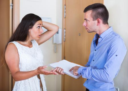 confundido: Retrato de arrendatario y arrendador confusa furioso con facturas pendientes de pago en el hogar