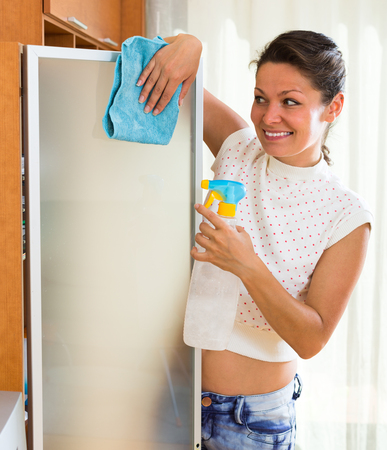 atomizer: Joyful smiling young woman cleaning glass with atomizer and shred Stock Photo