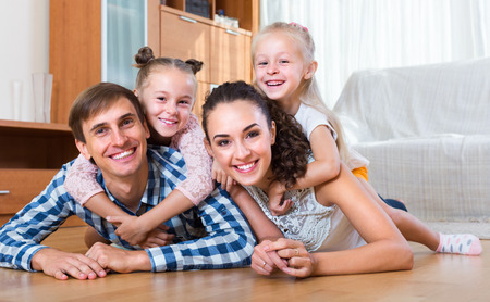 Family values: portrait of smiling parents with little girls indoors