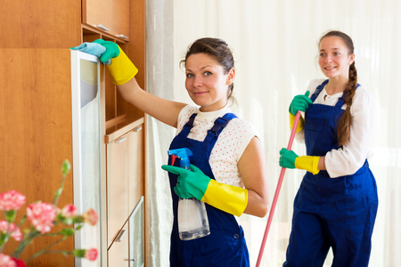 cleaning team: Happy young female workers cleaning company ready to start work Stock Photo