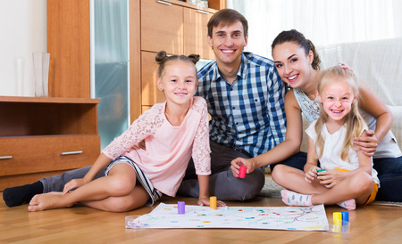 game room: Smiling young family of four playing at board game in domestic interior Stock Photo