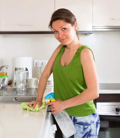 kitchen furniture: Woman cleaning furniture in kitchen at home