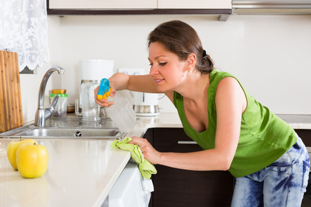 kitchen furniture: Young smiling woman cleaning furniture in kitchen at home