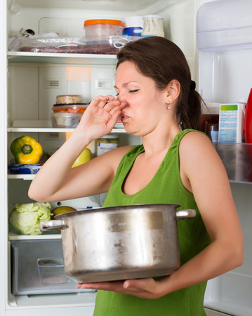 frowy: Young girl holding her nose because of bad smell from food near refrigerator  at home