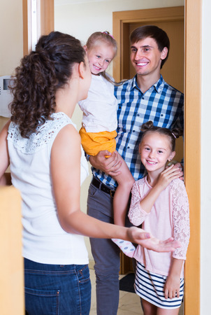 expected: Happy hospitable householder meeting expected guests at doorway and smiling