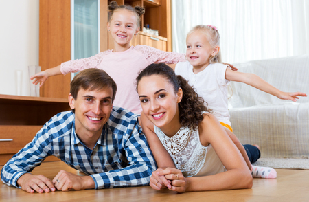 4s: Beautiful parents with two little daughters relaxing at home. Focus on the parents
