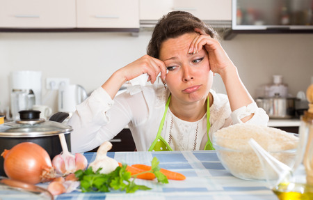 home appliances: Sad young housewife cooking dinner for her family Stock Photo