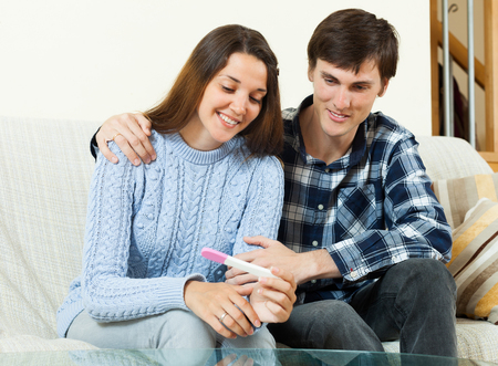 home pregnancy test: Smiling couple together with pregnancy test at home