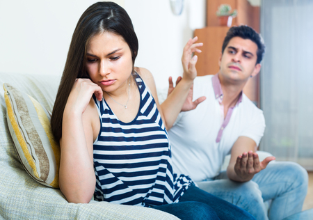 blaming: Young man and woman blaming each other during indoor quarrel