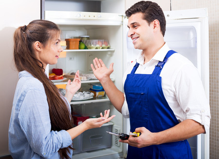 tooling: Young  housewife and cheerful handyman with tooling standing near fridge indoors