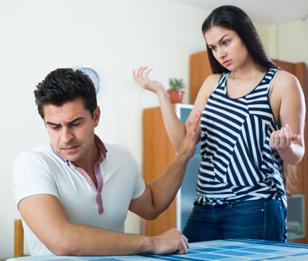enmity: Angry young spouses having domestic argue at a living room at home