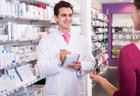 farmacia: Mujer de la porción farmacéutico en farmacia y sonriente Foto de archivo