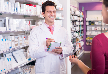 pharmacist: pharmacist serving  woman in pharmacy and smiling