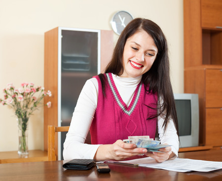 calculated: happy woman  with money and documents  in home interior Stock Photo
