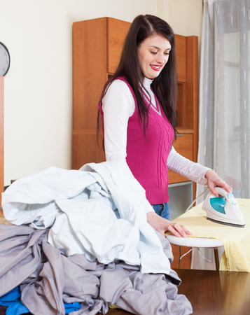 iron: brunette woman ironing with iron at  home