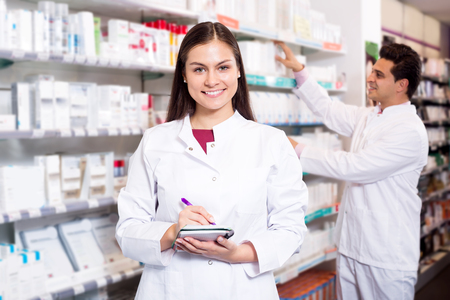 farmacy: Two happy friendly pharmacists working in modern farmacy Stock Photo