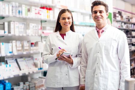 farmacia: Dos sonriente farmac�uticos c�modos que trabajan en farmacia de lujo Foto de archivo