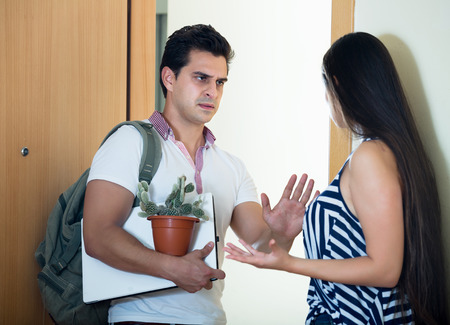 unfriendly: Frustrated young girlfriend watching man moving out with baggage