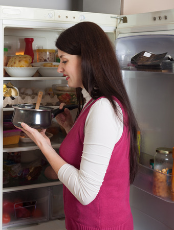 refrigerator kitchen: Brunette woman with small pan near opened refrigerator in kitchen at home