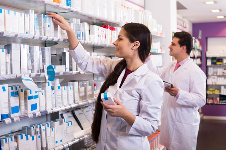 armenian woman: Positive adult pharmacist and pharmacy technician posing in drugstore