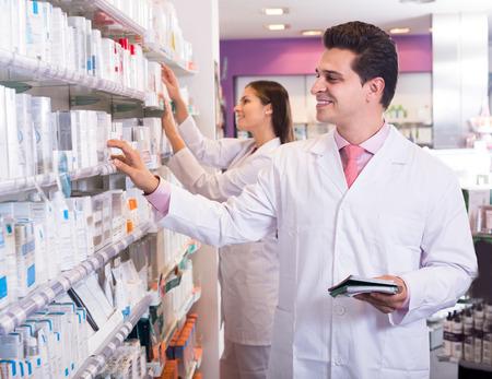 pharmacist: Smiling pharmacist and american pharmacy technician posing in drugstore Stock Photo